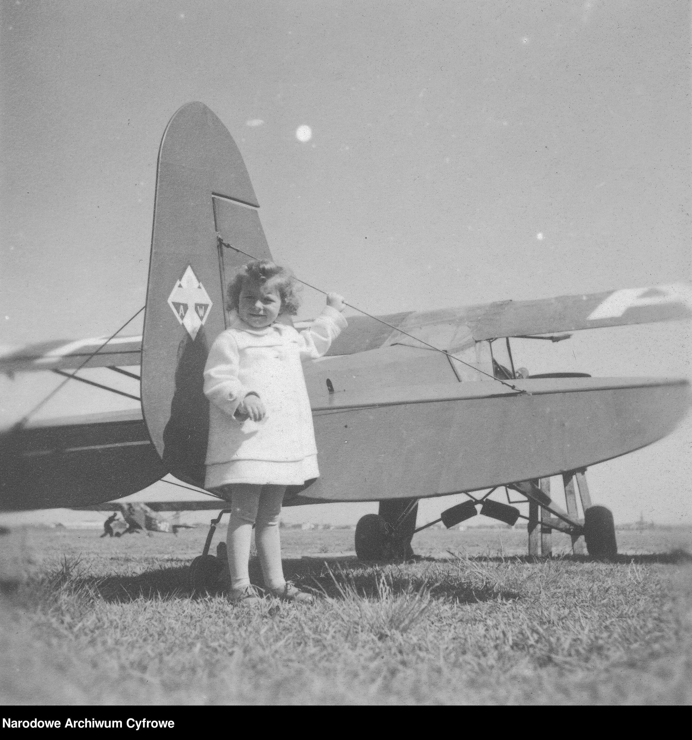 Czarno białe zdjęcie. Mała dziewczynka ubrana nabiało stoi przy starym samolocie.