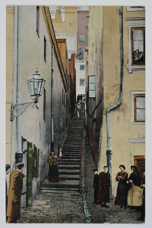Zdjęcie wąskie schody prowadzące fo góry między dwoma kamienicami.