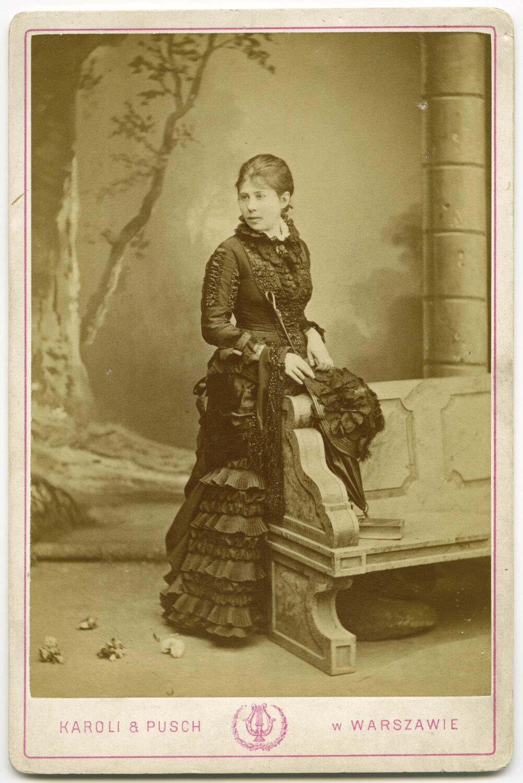 Czarno białe zdjecie. Kobieta wdługiej sukni pozuje wstudiu fotograficznym wzaaranżowanej scenografii.
