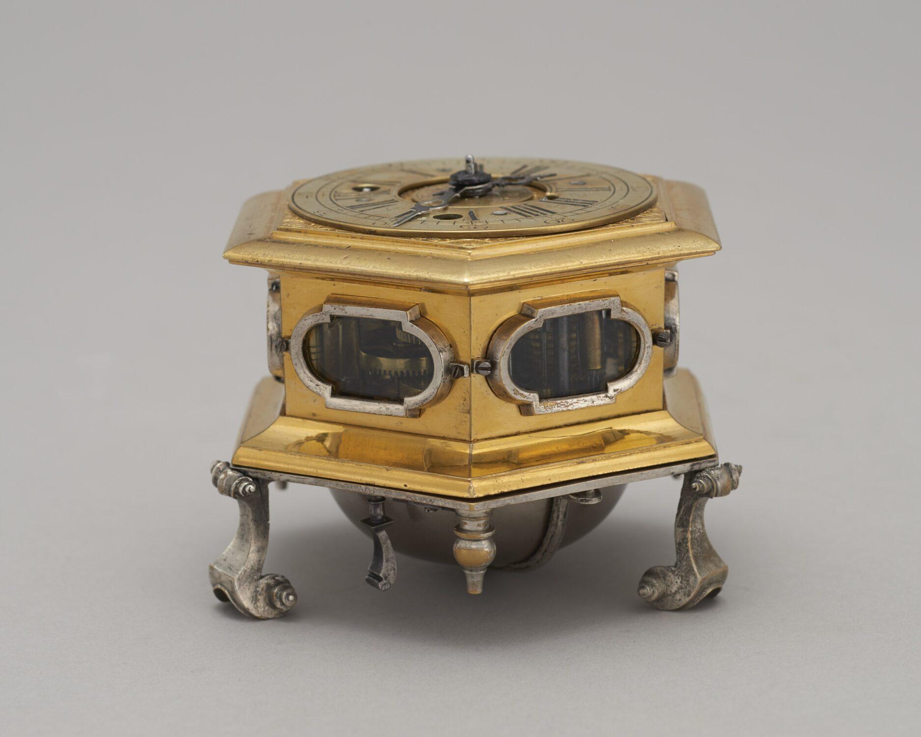 Zdjęcie zegara wformie szkatułki wkoloreze złota zlicznymi zdobieniami.