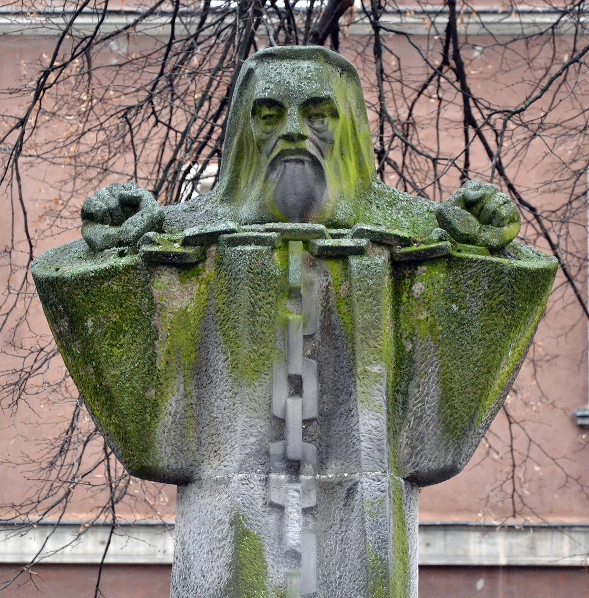 Fragment rzeźby męzczyzny zbrodą idługimi włosami, wdługiej szacie zrękami wkajdanach
