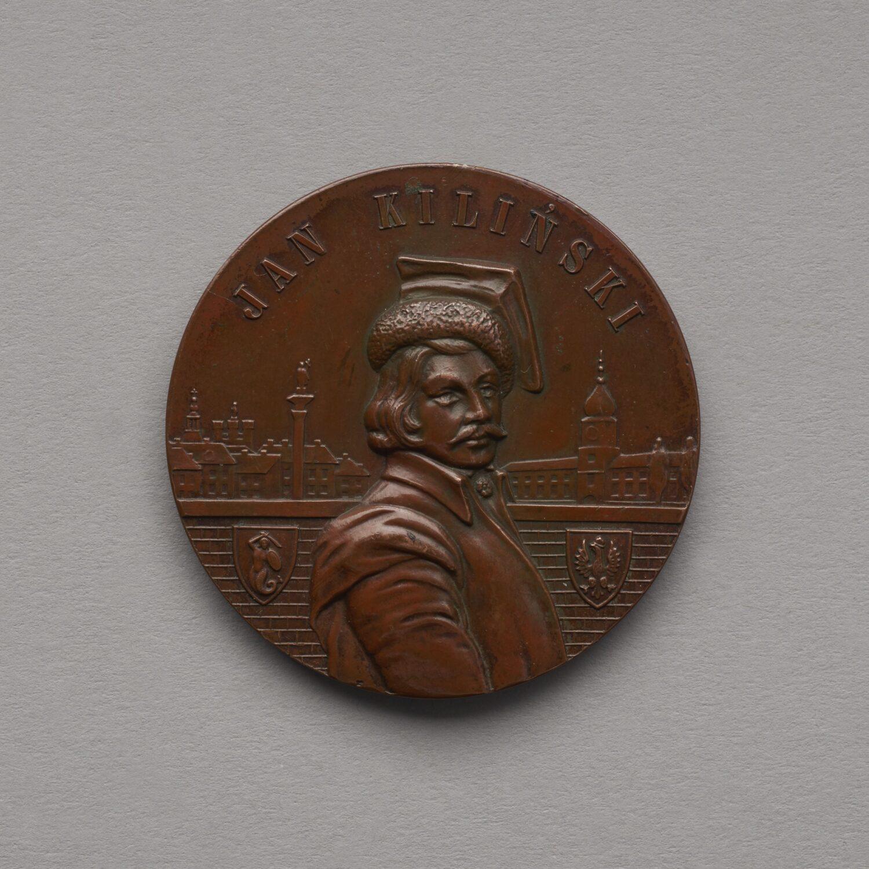 Zdjęcie okrągłego medalu wkolorze brązowy zwizerunkiem mężczyzny wczapce. Wtle zamężczyzną widok naZamek Królewski ikolumnę Zygmunta