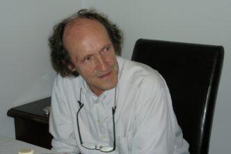 Zdjęcie mężczyzny siedzącego za biurkiem.