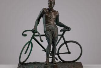 Posążek z brązu. Mężczyzna opierający się o rower
