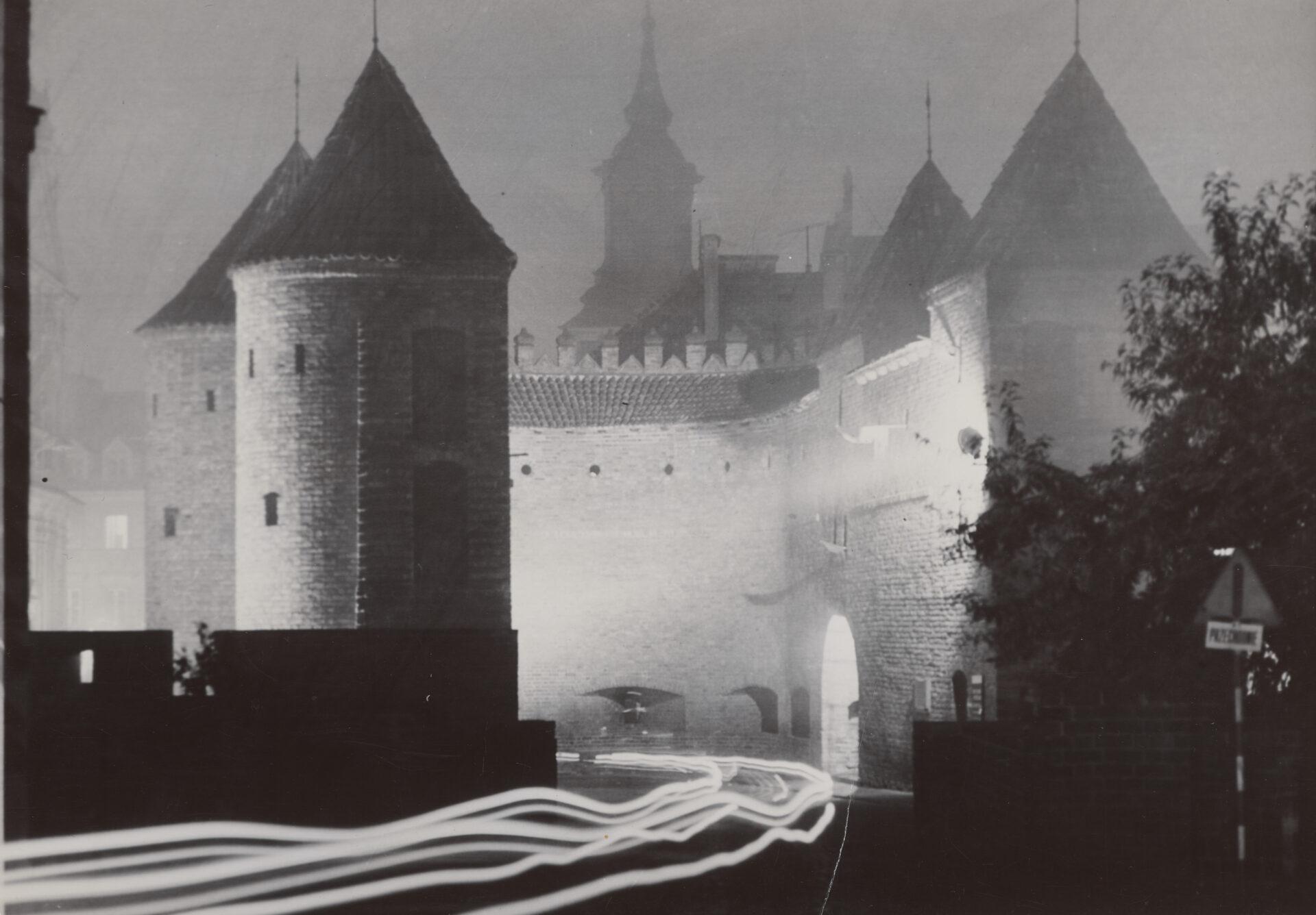 Czarno białe zdjęcie. Oświetlony Barbakan nocą