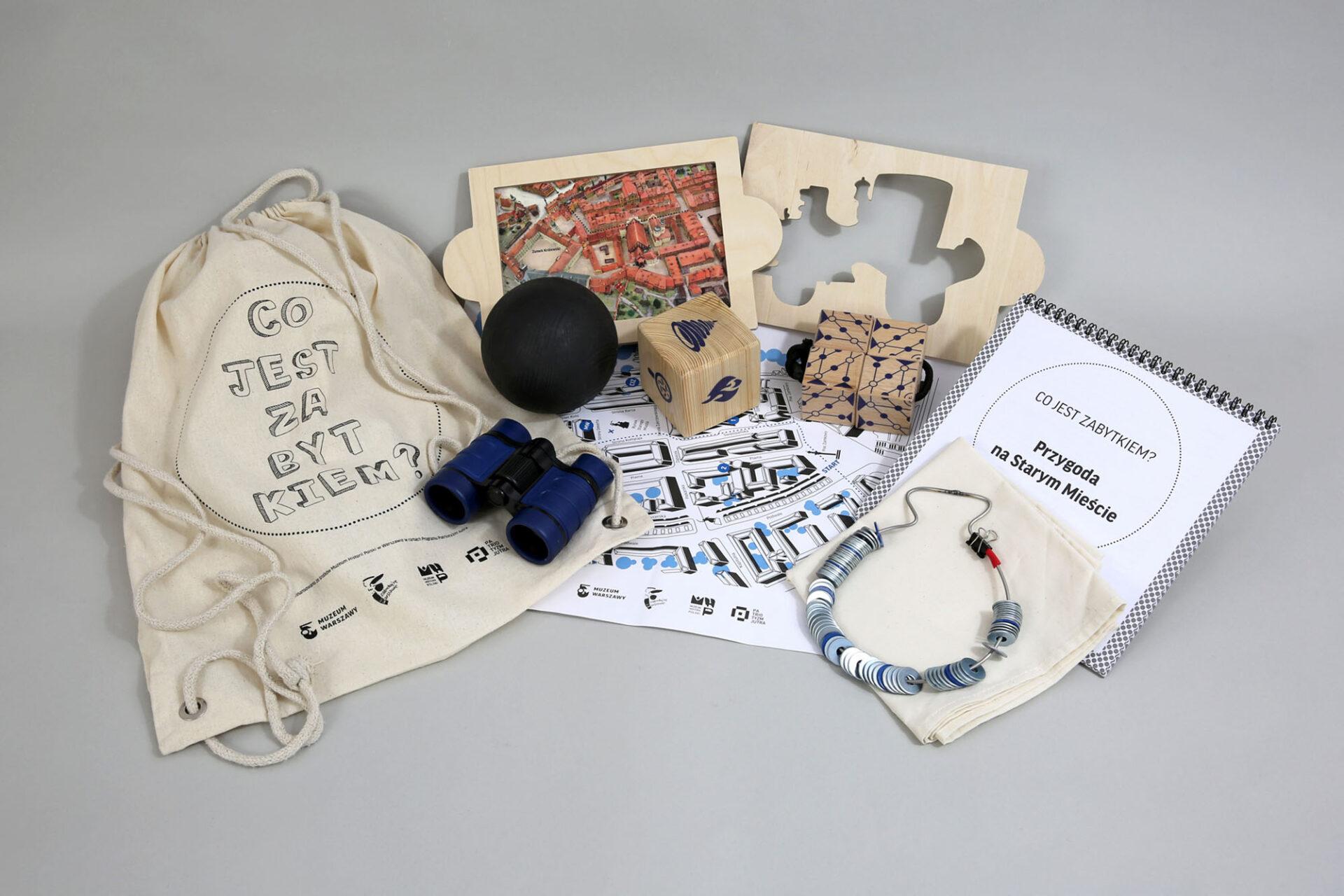 Zdjęcie. Naszarym tle rozłożone przedmioty. Płócienny plecak znapisem co jest zabytkiem, lornetka, mapa warszawy, notes, drewniane klocki, czarna piłka.