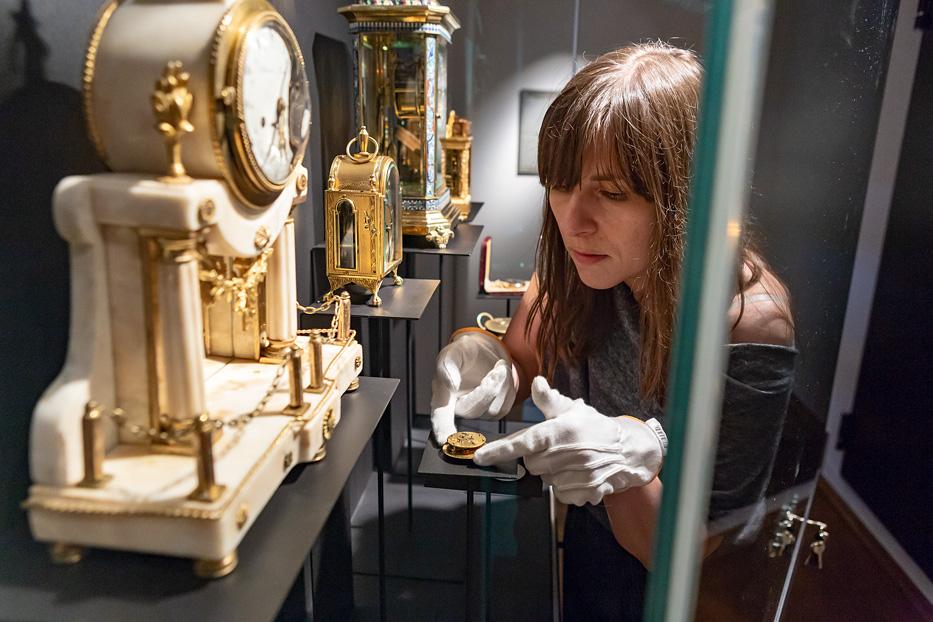 Pracownik muzeum wstawiający zegar do gabloty.