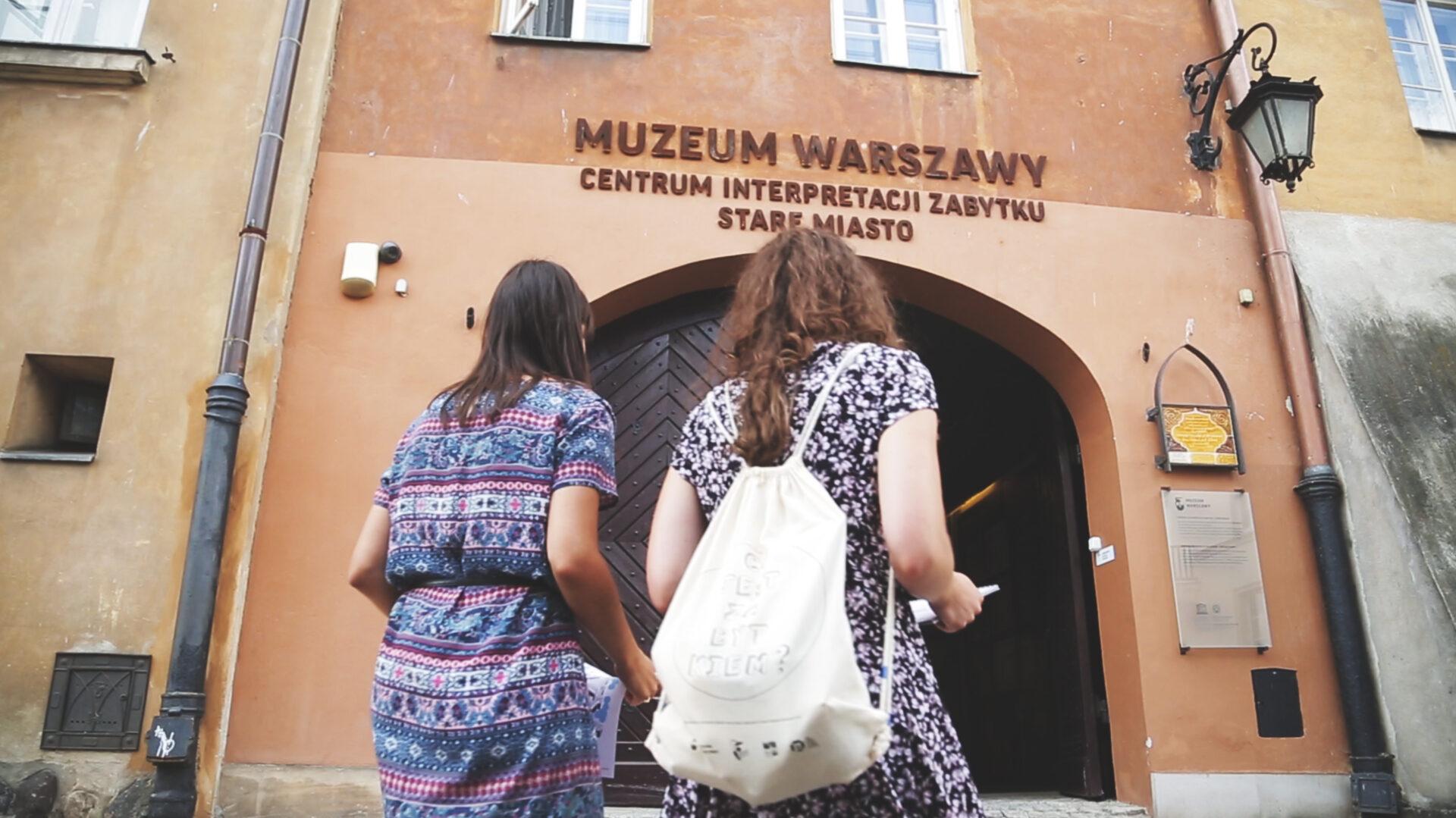 Dwie osoby przed wejściem do budynku. Nad drzwiami napis Muzeum warszawy Centrum Interpretacji Zabytku.