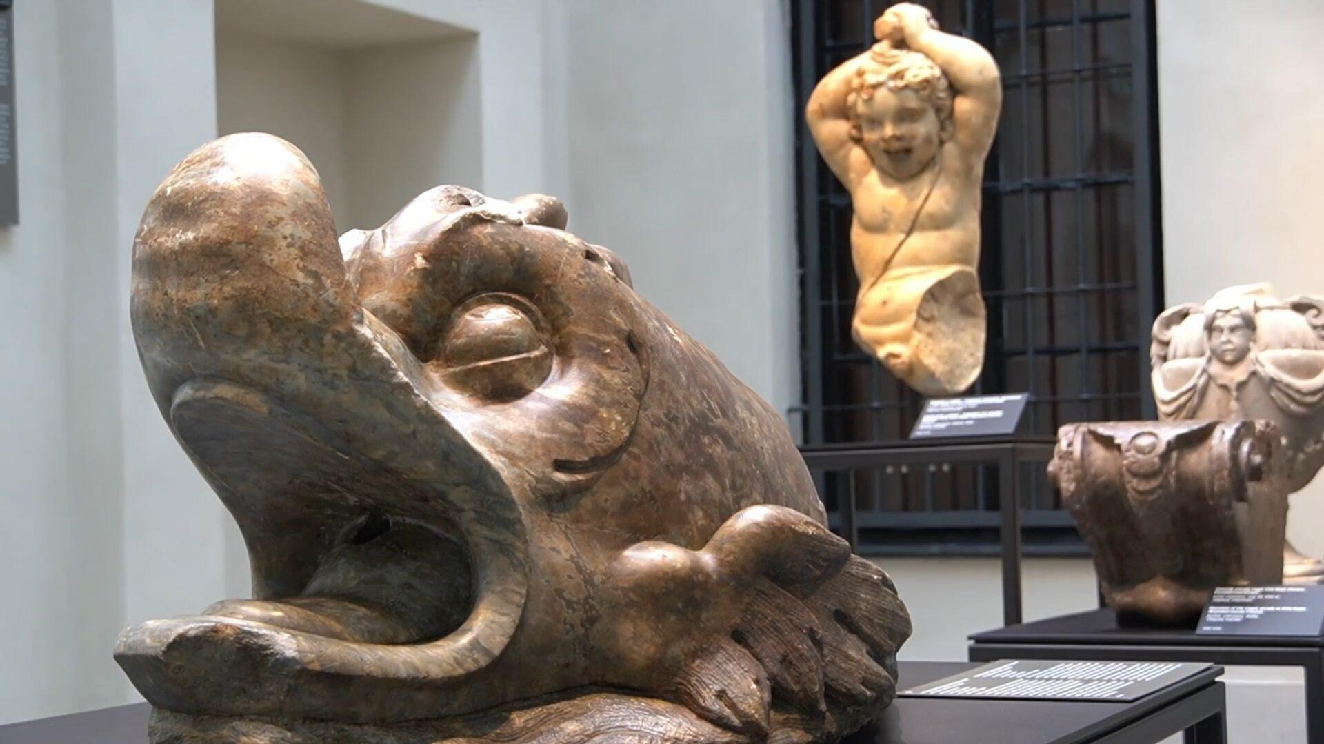 Zdjęcie. Kamienna rzeźba delfina wtle rzeźba putta