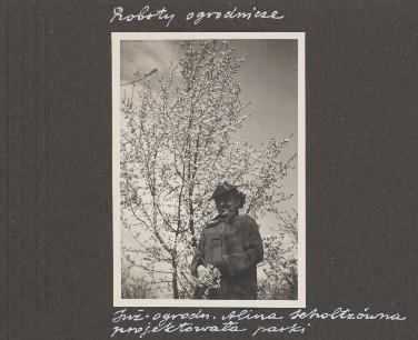 Czarno białe zdjęcie kobiety natle kwitnącego drzewa.