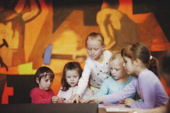 dzieci pochylają się nad stołem, pokazując sobie coś, w tle obraz fangora