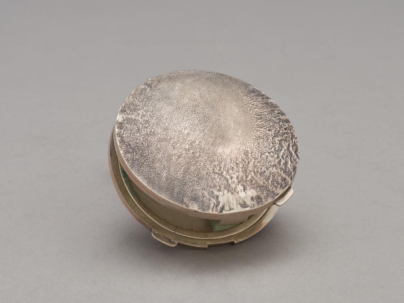 Zdjęcie srebrnej, okrągłej puderniczki. Nawieku nieregularna faktura, powstała poprzez rozgrzanie istopienie wierzchniej warstwy metalu.