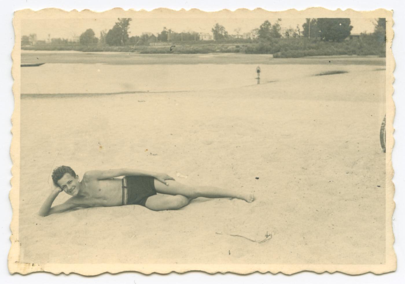 Fotografia. Nadbrzegiem Wisły, napiaszczystej plaży młody chłopak leży naprawym boku. Podpiera głowę naręce, uśmiecha się. Ubrany tylkowciemne krótkie spodenki. Wtle niewysokie drzewa ikrzewy.