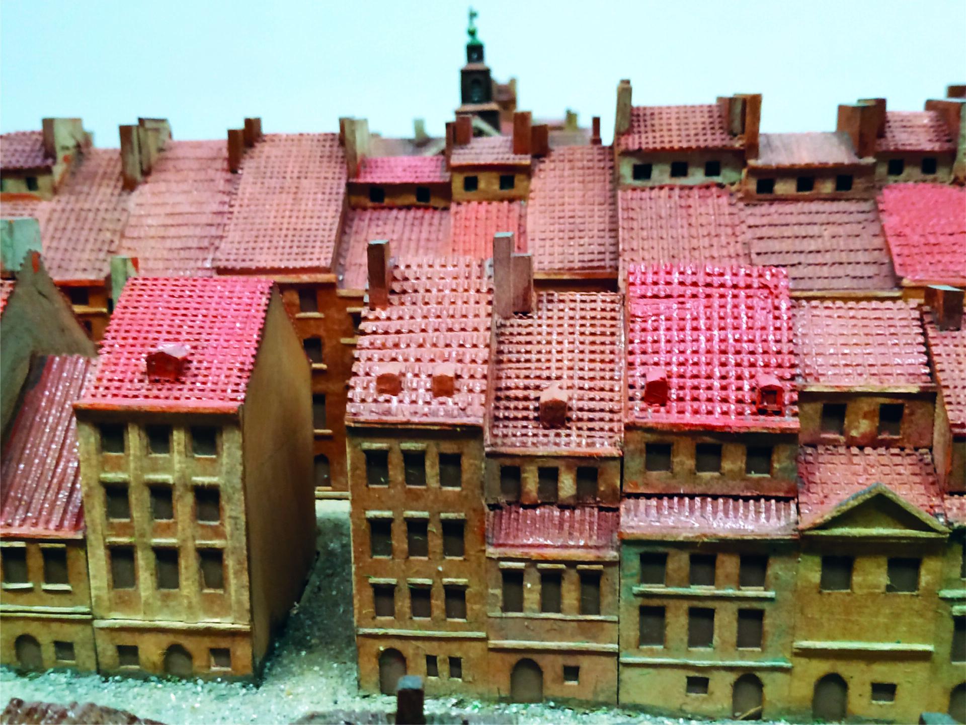 Fragment makiety Warszawy zMuzeum Warszawy. Napierwszym planie gęstą zabudowa kamienic krytych czerwoną dachówką. Wgłębi czerwone dachy kolejnych domów.