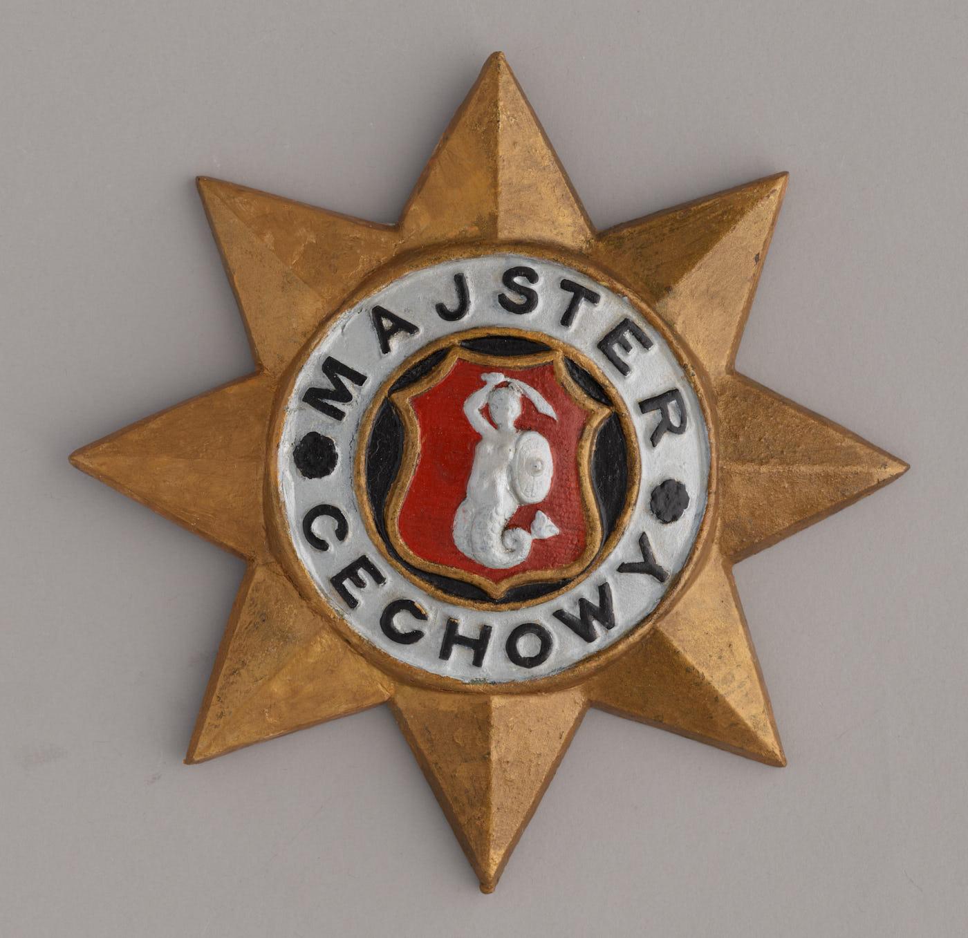 Żeliwna wywieszka wkształcie ośmioramiennej, złotej gwiazdy. Naśrodku herb Warszawy - biała syrena naczerwonym tle. Wokół herbu, nabiałym tle granatowy napis: Majster cechowy.