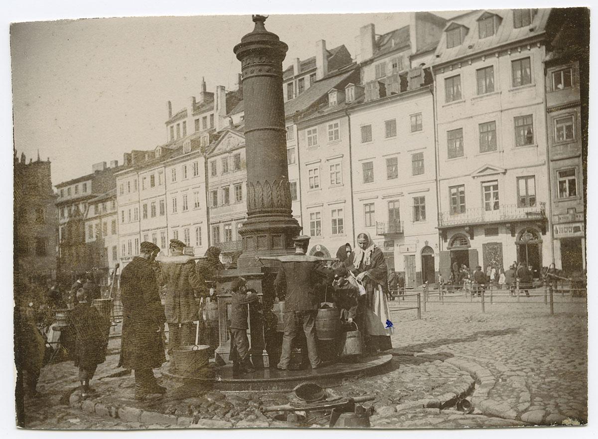 Czarno biała fotografia. Napierwszym planie wysoka pompa przy Rynku Starego Miasta. Wokół niej mężczyźni, kobiety idzieci napełniają wiadra wodą. Wtle rząd kamienic.