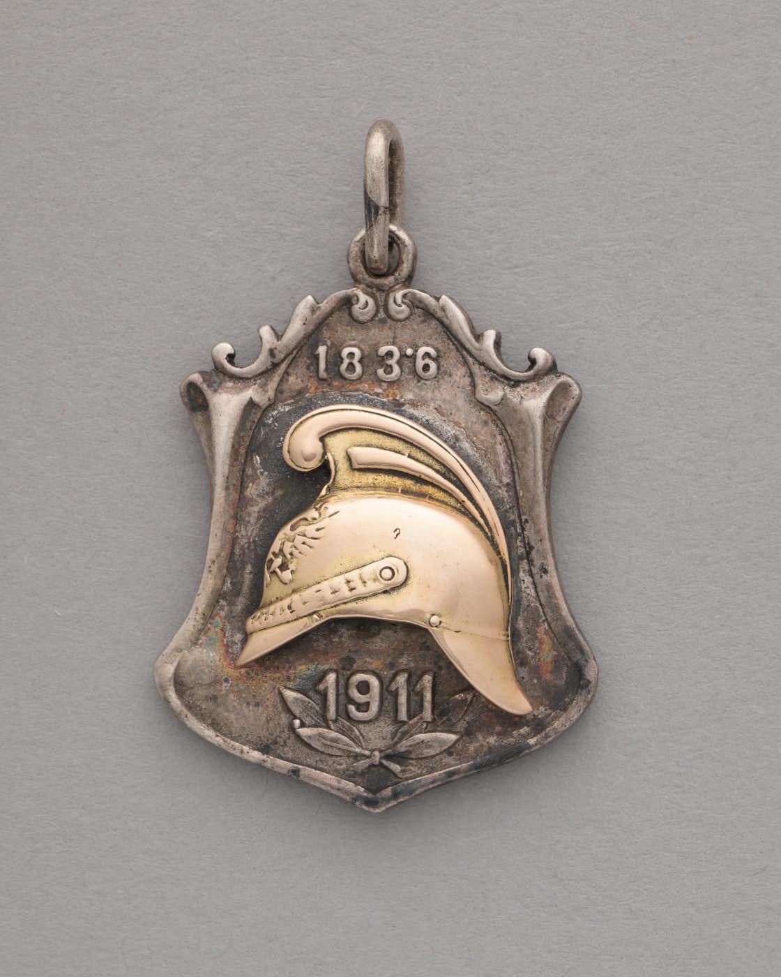Srebrna odznaka wkształcie trapezu. Dolna krawędź uformowana wzaokrąglony szpic. Górna, wpodobnym kształcie, dodatkowo fantazyjnie pofalowana. Naśrodku pozłacany hełm strażacki. Nadnim data roczna 1836, podnim 1911. Ugóry uszko dozawieszenia.