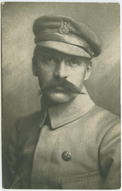 Czarno-białe zdjęcie portretowe Marszałka Piłsudskiego. Ubrany wmundur iczapkę wojskową – maciejówkę zorłem. Wzrok skierowany ku górze, prosty nos icharakterystyczne, sumiaste wąsy zasłaniające usta.