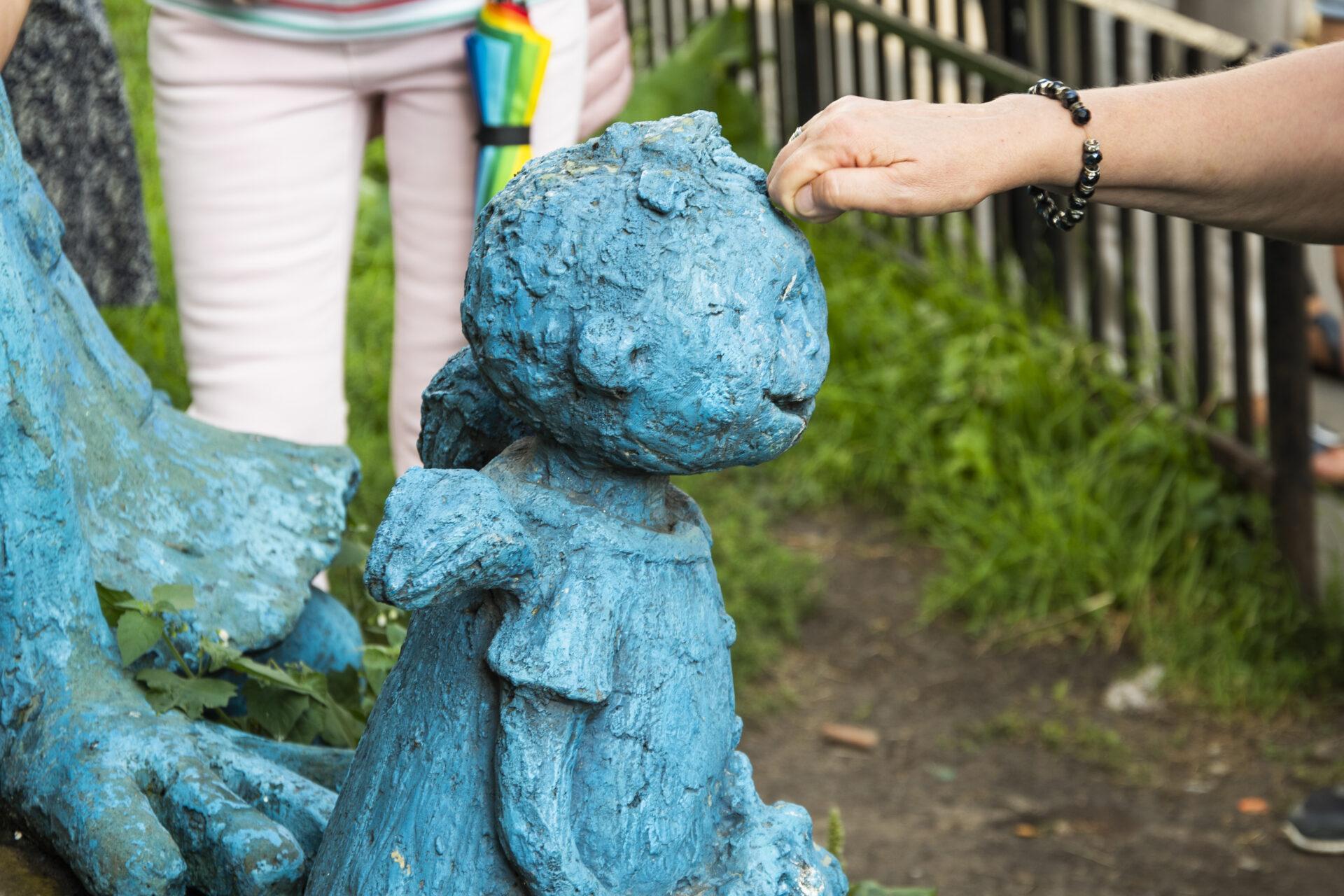 zwinięta wpięść dłoń stuka wczoło rzeźby anioła, anioł jest niebieski, pyzata twarz, uśmiech, ubrany wsukienkę