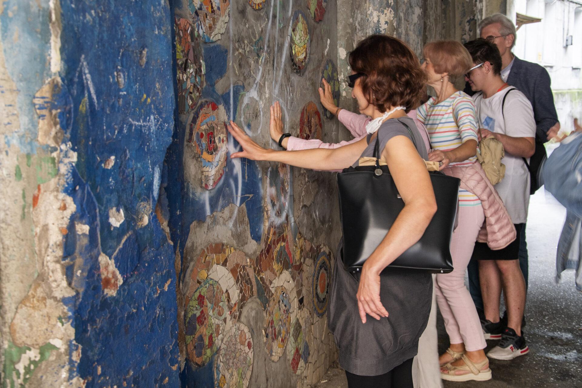 Grupa osób wróżnym wieku zzamkniętymi oczami dotyka mozaiki naścianie. Kilkanaście wielokolorowych kół onierównej powierzchni. Posklejane zróżnokształtnych fragmentów, przypominających kawałki stłuczonego szkła.