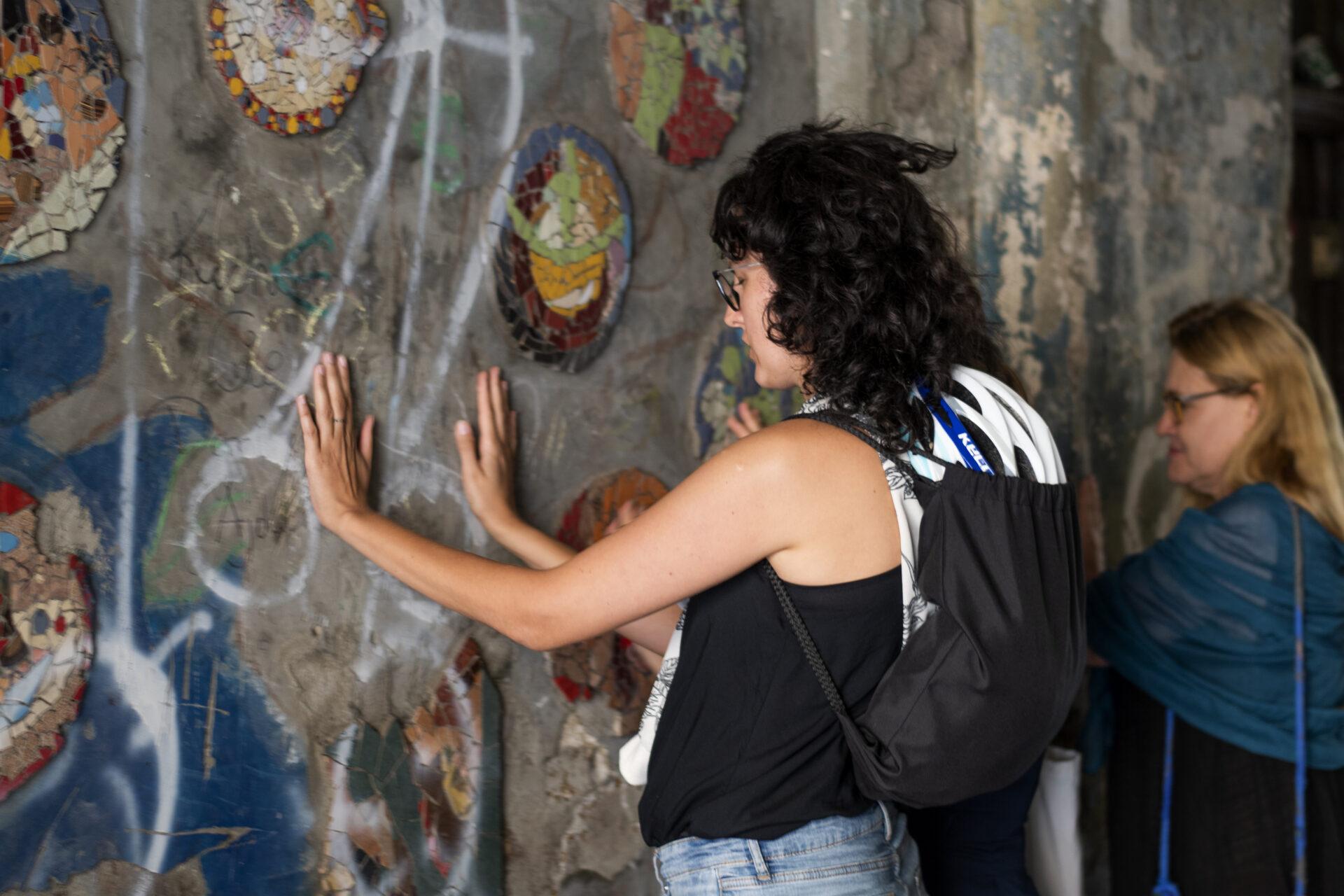 Kobieta wkręconych włosach, wokularach zmałym plecakiem stoi przedścianą. Jest skupiona, wyciągnięte ręce trzyma naścianie pomiędzy elementami mozaiki.
