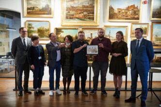 ubrani elegancko uczestnicy wydarzenia stoją w rzędzie pozują do zdjęcia na tle obrazów z widokami Warszawy