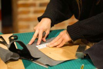 stół w pracowni, na zielonej podkładce leżą kawałki materiału, który dociskają dwie dłonie, obok leżą nożyczki i skrawki innych materiałów