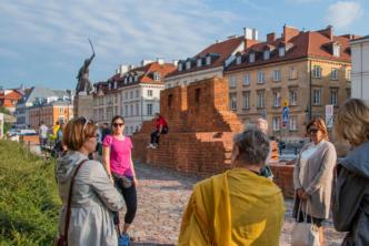 kilka osób w kółku słucha przewodniczki, w tle fragment murów barbakanu i kamienice starego miasta