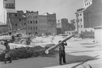 czarno biała fotografia, w tle ruiny kamienic, usypane gruzy, piach, robotnicy, samochody, na pierwszym planie idzie pochylony mężczyzna z żerdzią na ramieniu