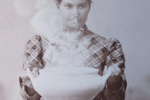 zdjęcia sepia, młoda dziewczyna w sukience w kratkę trzyma przed sobą misę z zupą, zupa paruje, para zasłania twarz dziewczynie